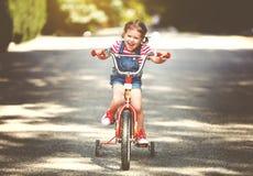 Glücklicher Kindermädchenradfahrer, der ein Fahrrad reitet Stockbild