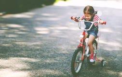 Glücklicher Kindermädchenradfahrer, der ein Fahrrad reitet Stockfoto