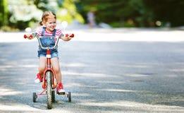 Glücklicher Kindermädchenradfahrer, der ein Fahrrad reitet Lizenzfreie Stockbilder