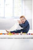 Glücklicher kleiner Junge, der auf Fußboden spielt Stockfotos