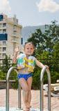Glücklicher kleiner Junge, der am Kamera Poolside wellenartig bewegt Stockfotografie