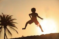 Glücklicher kleiner Junge, der am Sonnenuntergangstrand springt Stockfotos