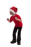 Glücklicher kleiner Junge im Hut von Santa Claus dieses Weihnachten genießend kommt auf weißen Hintergrund Lizenzfreies Stockbild