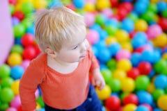 Glücklicher Kleinkindjunge, der in der Ballgrube spielt Lizenzfreies Stockfoto