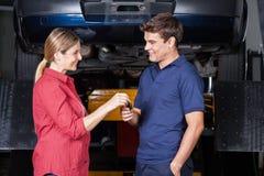 Glücklicher Kunde, der dem Mechaniker Auto-Schlüssel gibt Stockbild