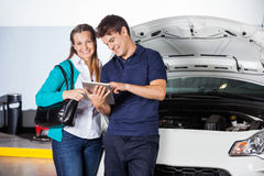 Glücklicher Kunde, der mit Mechaniker Using steht Lizenzfreie Stockbilder