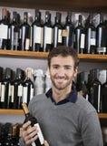 Glücklicher Kunde, der Wein-Flasche im Supermarkt hält Lizenzfreies Stockbild