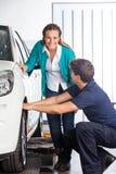 Glücklicher Kunden-bereitstehender Mechaniker Changing Tire Lizenzfreies Stockfoto