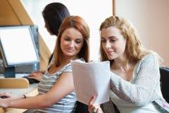 Glücklicher Kursteilnehmer, der ihrem Mitschüler ihre Anmerkungen zeigt Stockfoto