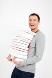 Glücklicher Kursteilnehmer mit einem Stapel Büchern Stockbilder