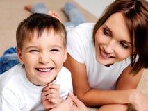Glücklicher lachender Vorschülerjunge mit seiner Mutter Stockbild