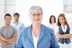 Glücklicher älterer Lehrer mit Kursteilnehmern im Hintergrund Stockbild