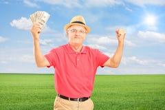Glücklicher älterer Mann, der Geld hält und Glück auf einem Feld gestikuliert Stockbild