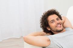 Glücklicher Mann, der auf Sofa stillsteht Stockfotografie