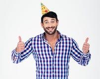 Glücklicher Mann im Parteihut, der sich Daumen zeigt Stockbild