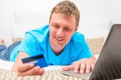 Glücklicher Mann mit einer Kreditkarte Stockbild