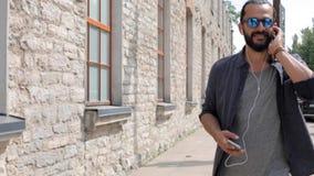 Glücklicher Mann mit Kopfhörern über dem Gehen in Stadt 11 stock video footage