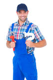 Glücklicher männlicher Klempner, der Universalschraubenschlüssel und Abflussrohr hält Lizenzfreies Stockfoto