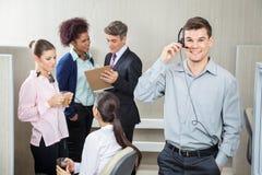 Glücklicher männlicher Kundendienstmitarbeiter Using Stockfoto