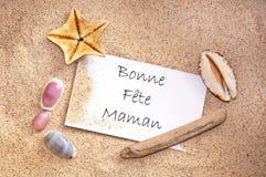 Glücklicher Muttertag geschrieben auf französisch auf eine Anmerkung mit Sand Stockfotos