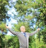 Glücklicher reifer Herr, der einen Stock hält und seine Arme verbreitet Stockbild