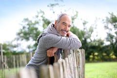 Glücklicher reifer Mann in der Landschaft, die auf hölzernem Zaun sich lehnt Stockbild