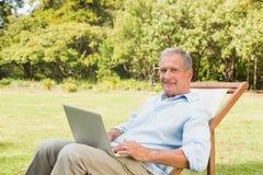 Glücklicher reifer Mann, der Laptop verwendet Stockfotos