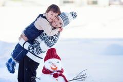 Glücklicher schöner Familiengebäudeschneemann im Garten, Winterzeit, Stockfotografie