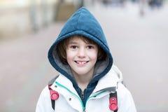 Glücklicher Schuljunge, der auf eine Straße mit einem Rucksack an einem kalten Tag geht Stockfoto