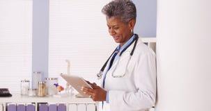 Glücklicher schwarzer älterer Doktor, der im Büro mit Tablette steht Stockfotografie