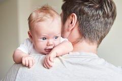 Glücklicher Vater, der neugeborenes Baby in seinen Armen hält Stockfotografie