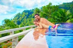 Glücklicher Vater und Sohn, die im Unendlichkeitspool auf Tropeninsel sich entspannt Stockfotografie
