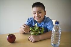 Glücklicher vorjugendlicher Junge, der Salat isst Lizenzfreies Stockfoto