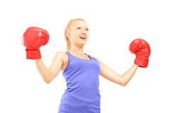 Glücklicher weiblicher Athlet, der rote Boxhandschuhe trägt und Zufall gestikuliert Lizenzfreie Stockfotografie