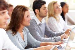 Glücklicher weiblicher Kursteilnehmer mit Computer Lizenzfreie Stockbilder