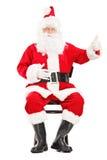 Glücklicher Weihnachtsmann, der auf einem Holzstuhl sitzt und einen Daumen u gibt Lizenzfreie Stockbilder