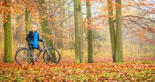 Glückliches aktives Frauenreitfahrrad im Herbstpark Stockbild