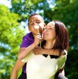 Glückliches allein erziehende Mutter mit Schlaglöwenzahn des Sohns Stockfotos
