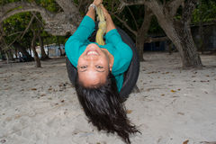 Glückliches asiatisches Mädchenreiten auf dem Schwingen gemacht vom Reifen am Strand Stockbilder