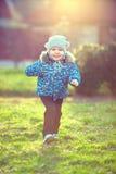 Glückliches Baby, das den sonnenbeschienen Frühlingspark laufen lässt Stockbild