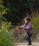 Glückliches Baby, das Löwenzahn spielt Lizenzfreies Stockfoto