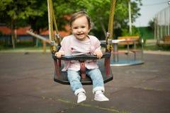Glückliches Baby gibt im Schwingen Stockbild