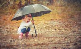 Glückliches Baby mit einem Regenschirm im Regen, der auf Natur spielt Stockbild