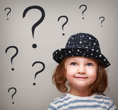 Glückliches denkendes Kindermädchen im Hut, der oben schaut Lizenzfreie Stockfotografie