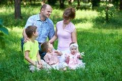 Glückliches Familienporträt auf im Freien, Gruppe von fünf Leuten sitzen auf Gras im Stadtpark, -Sommersaison, -kind und -elternt Stockfotos