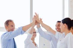 Glückliches Geschäftsteam, das Hoch fünf im Büro gibt Stockfotografie