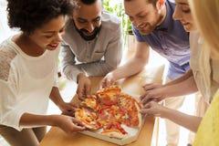 Glückliches Geschäftsteam, das Pizza im Büro isst Stockbild