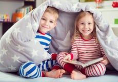 Glückliches Geschwisterlesebuch unter Abdeckung Stockfoto