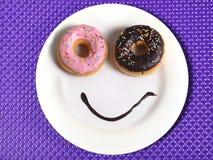 Glückliches Gesicht des smiley gemacht auf Teller mit Schaumgummiringaugen und Schokoladensirup als Lächeln im Zucker und in der  Stockbild