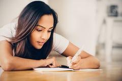 Glückliches indisches Studentin-Ausbildungsschreibensstudieren Stockfoto